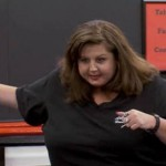 Abby Lee, going on a tirade in front of one of her many ironic motivational posters.